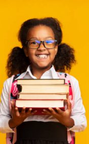 Excited Black Schoolgirl Holding Stack Of Books Smiling At Camera On Yellow Background. Studio Shot, Copy Space