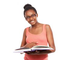 Studio portrait of a young african american girl reading a book and wearing glasses isolated on white